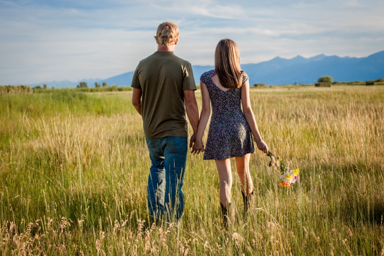 Young couple walking through a pasture on a summer day